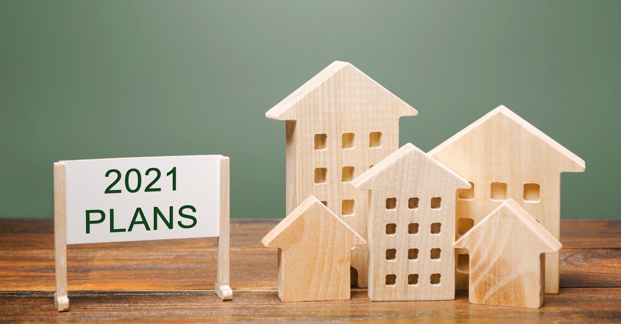 A poster with the words Plans 2021 and wooden houses. Real estate planning and financing concept